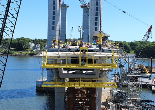 A large crane erects precast bridge segments into balanced cantilever at the Sarah Mildred Long Bridge. Photo courtesy of FIGG.